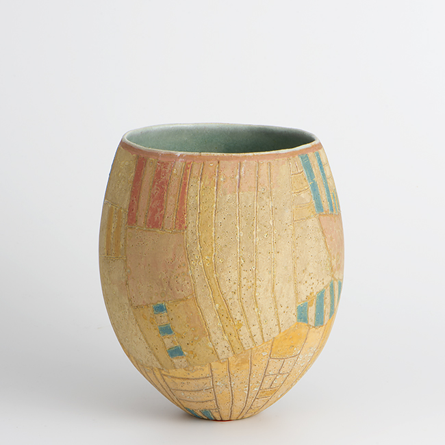 A pinched and decorated form using slips.